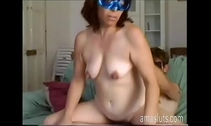 Mature woman in mask copulates with younger